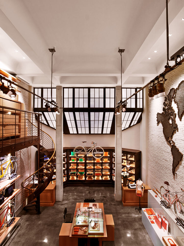 Industrial Tribeca space renovated by Rockwell Group for Shinola with white oak tables, poured concrete floors and vaulted ceiling with skylight