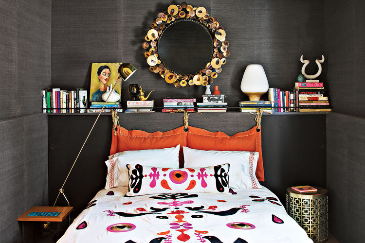 modern bedroom with black cloth covered walls and red and blue pattern bedspread