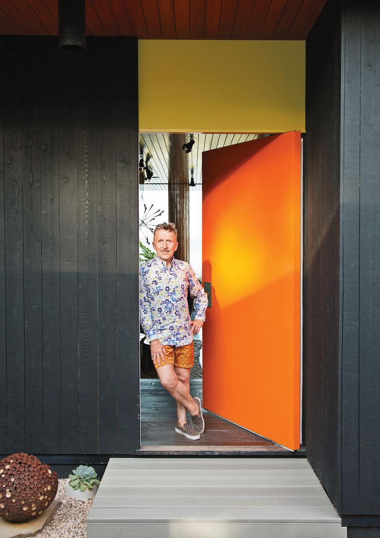 orange door of a black steel-framed home
