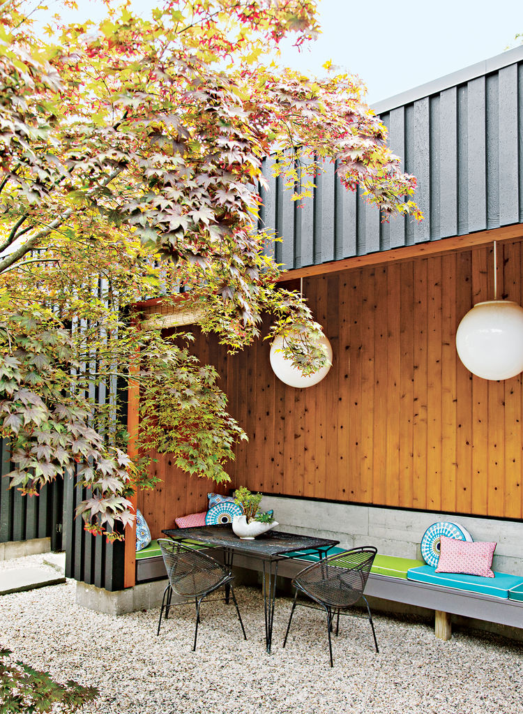 a gravel-lined courtyard features vintage metal outdoor table and chair and a cedar wood wall under the steel overhang of the roof