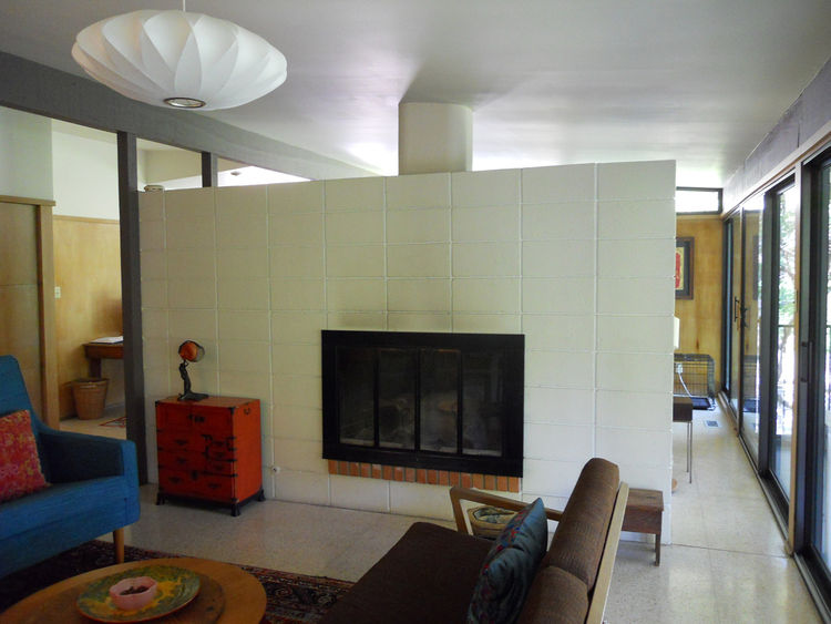the dark living room prior to renovation with an unsealed fireplace