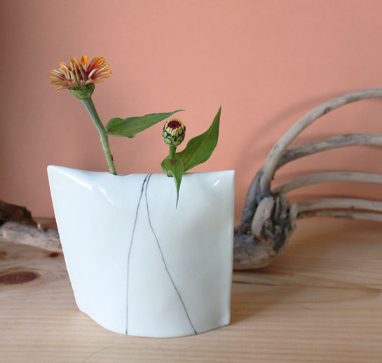 a square ceramic vase painted to resemble a pillow case