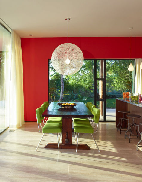 lime green chairs around a dark wood table in a red room full of sunshine