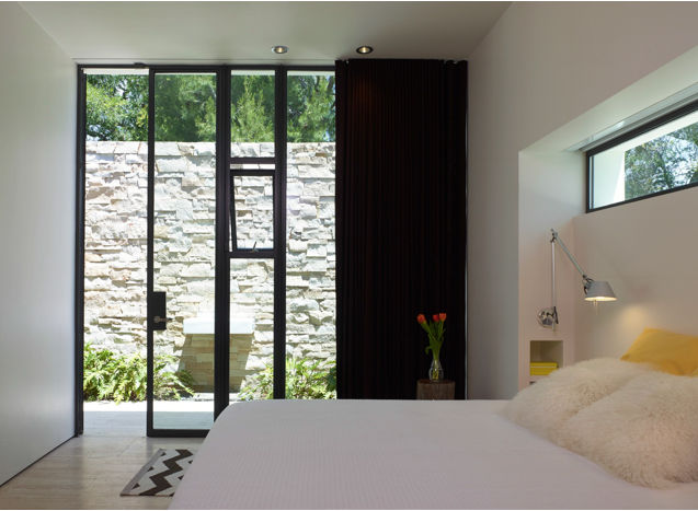a wall of windows between the bedroom and the courtyard