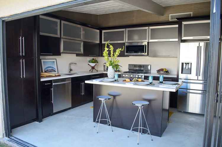 midcentury kitchen with black cabinets and stainless steel
