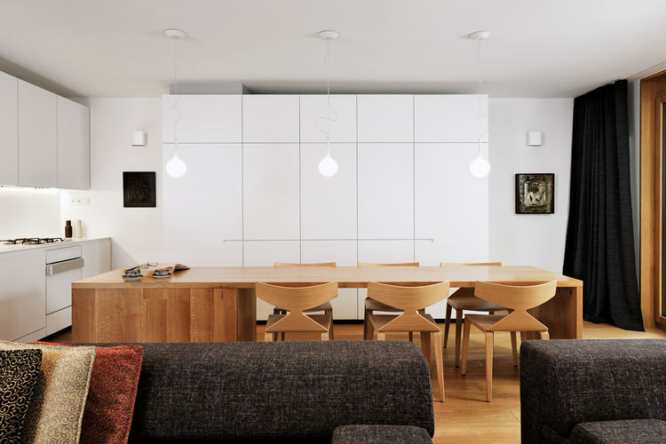 renovated apartment with white cabinets and wood dining table