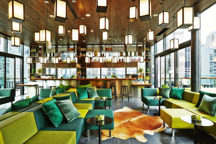 rooftop bar with green sofas and overhead lanterns
