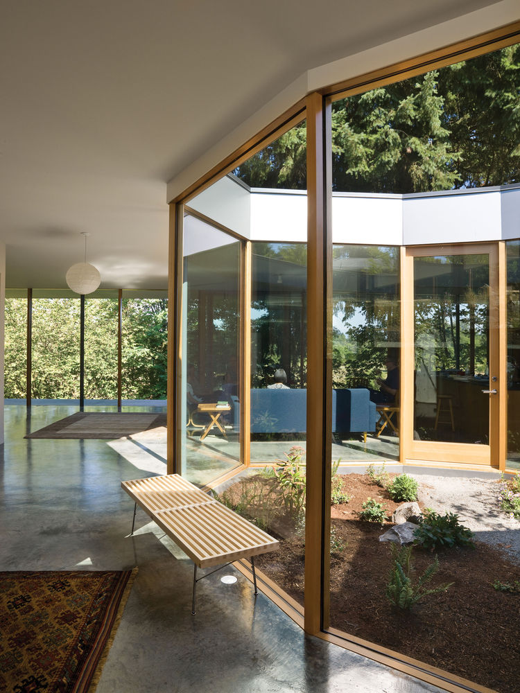 Interior of a modern home with floor to ceiling windows with views of trees