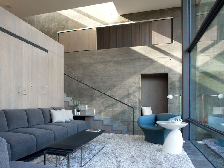 Llimestone flooring and stained oak cabinetry with concrete walls in a small space home in California by Cooper Joseph Studio.