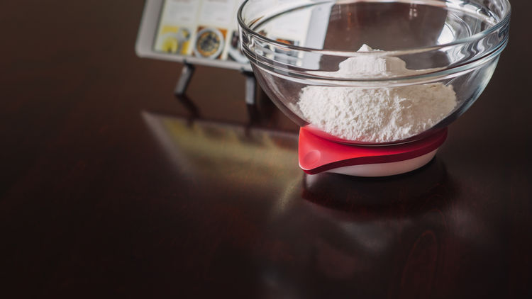 Drop scale with bowl of flour on black table