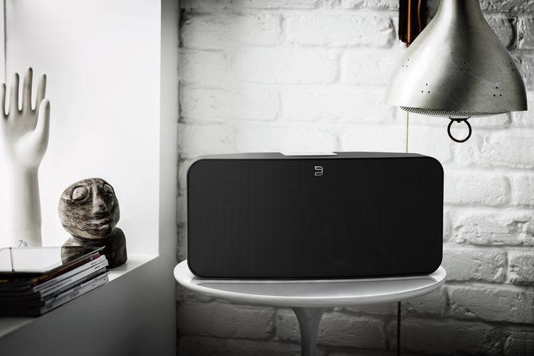 Bluesound wifi speaker on table in black.