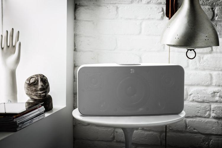 Bluesound wifi speaker on table in white.