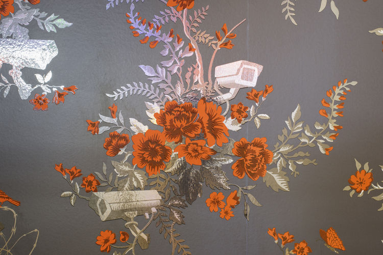 Floral scratch-and-sniff wallpaper with security cameras