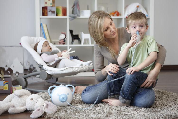 Nosiboo nasal aspirator used by boy and mom.