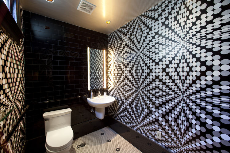 Bathroom with a graphic, optical black and white wallpaper