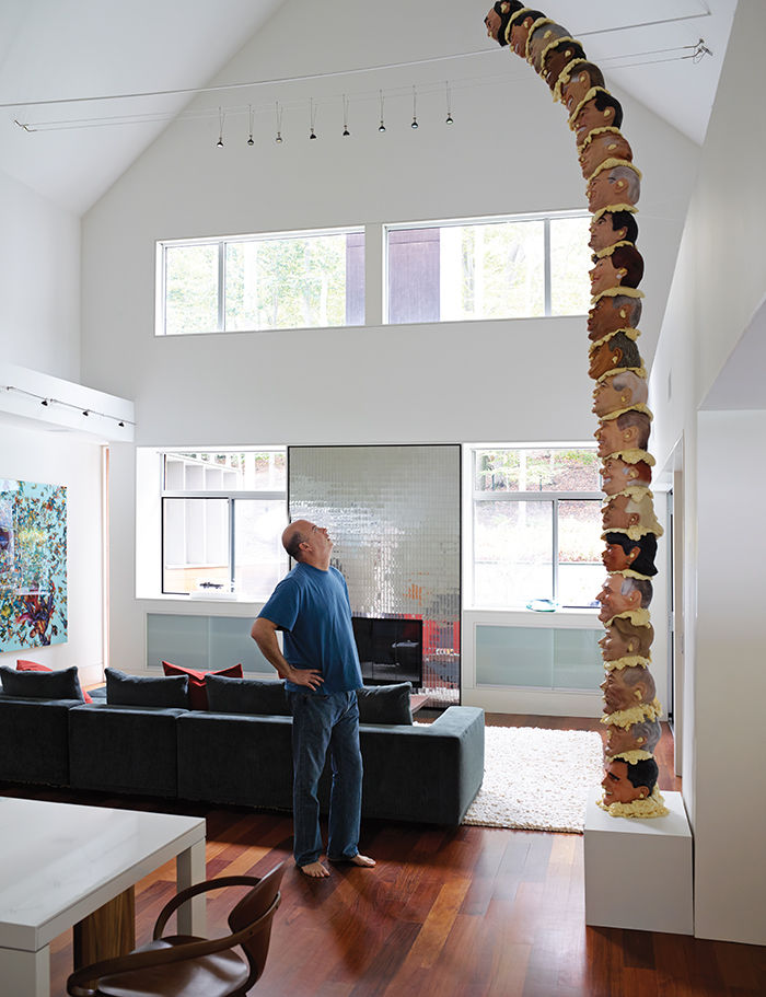 Hamptons living room with towering head sculpture and metallic fireplace