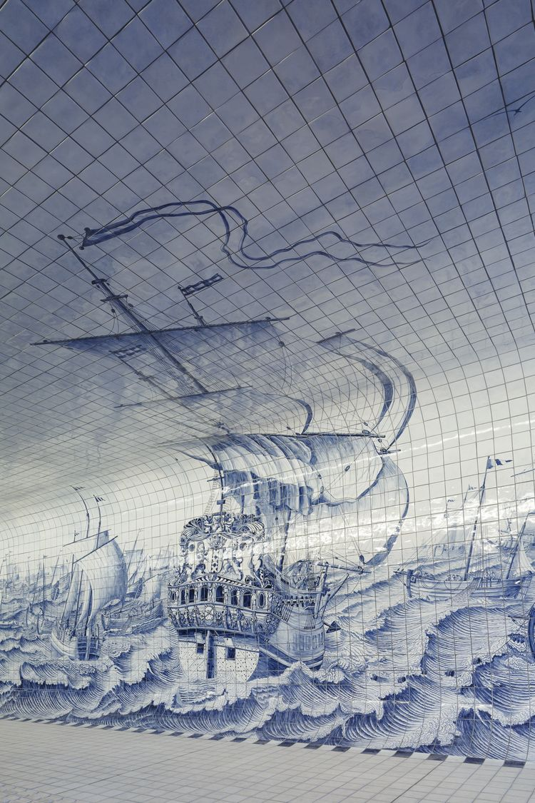 Dutch warship depicted in Delft blue tiles in Amsterdam tunnel.