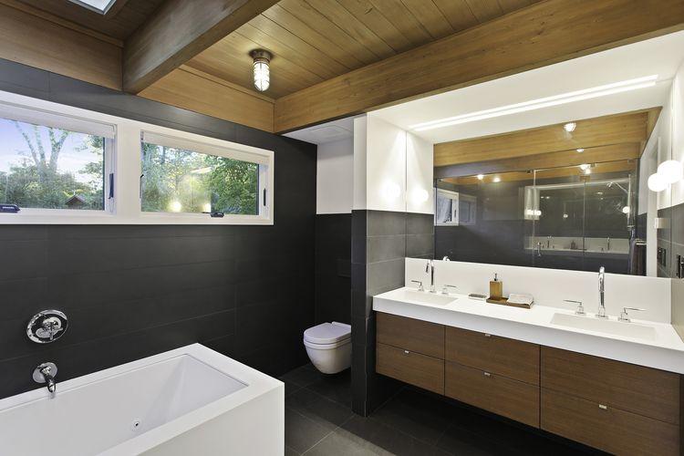 Corian Glacier White countertop, Zuma bathtub, and Lacava Cigno faucets in bathroom of Westchester renovation by Khanna Shultz.