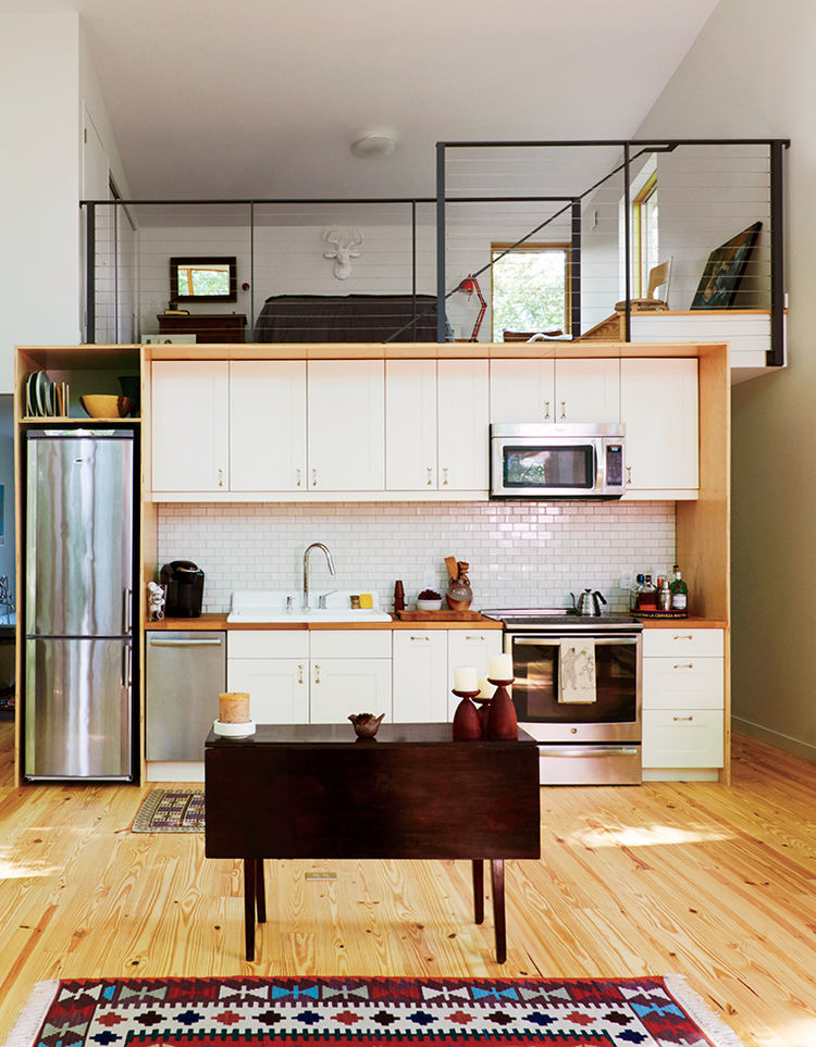 Modern small cantilevered cabin in Massachusetts with Summit refrigerator, ikea cabinets, and heath ceramics tiles in the kitchen and lofted bedroom