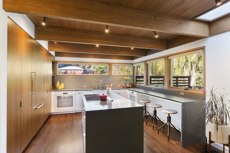 Caesarstone countertops and Basaltina tile backsplash by Stone Source in kitchen of Westchester renovation by Khanna Shultz.