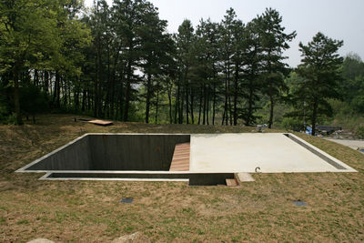 A square hole in the ground and a concrete slab are all that demarcate Byoung Cho's Earth House from the surrounding countryside.