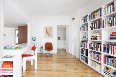 modern light-filled interior with white walls and built-in bookshelf