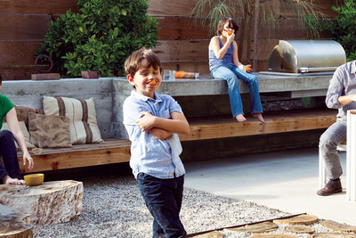 a shot of children in the family backyard sitting on a concrete bench
