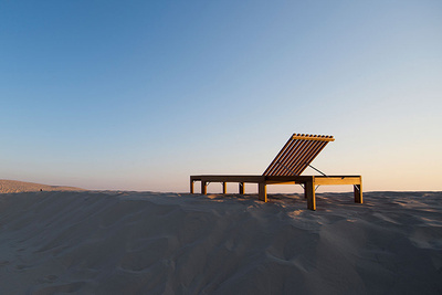 teak lounge chair in the sand