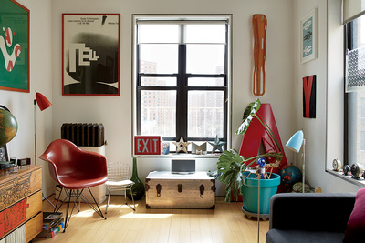Bright modern living room renovation with red chair and graphic prints