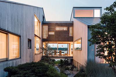 head of its class connecticut renovation summer home facade bleached cedar siding volumes glass bridge