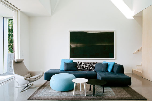 Concrete floor, white walls, Bend sectional sofa, Metropolitan chair by B&B Italia, and Arper pouf in living room of Rhode Island family vacation home by Bernheimer Architecture.