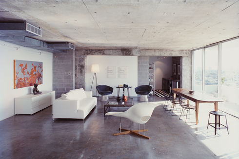 A Philippe Starck standing lamp and an Eames chaise longue bracket the living room; two Lawrence Weiner prints hang behind a pair of Warren Platner chairs and a table purchased from a River Oaks estate sale; at far left of the room, a partial wall of new