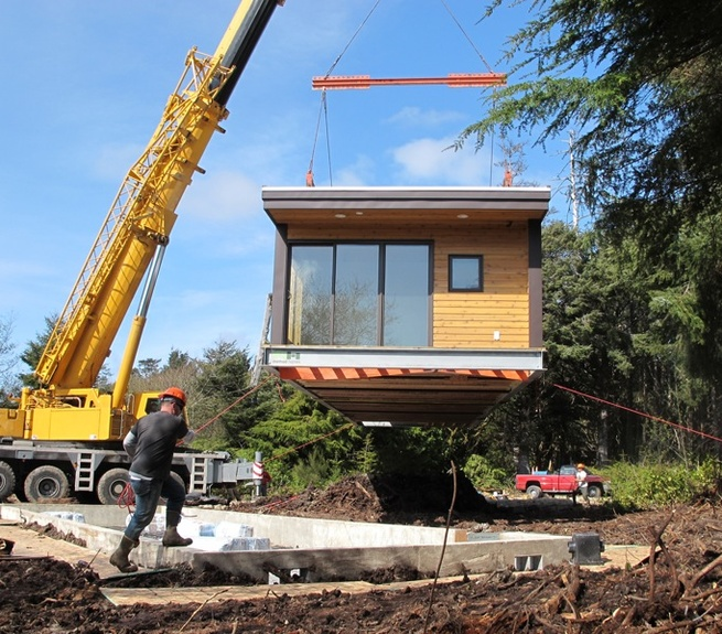 A Method Homes house is placed onto its foundation by a crane. Once production begins, the project will be completed within two to three months.
