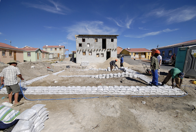 "Before building the framework of the house with pine timber and galvanized metal, the workers piled sandbags on the ground to map out the home's foundation. Image courtesy <a href=http://www.interactiveafrica.com"">Interactive Africa</a>/<a href=http://www"