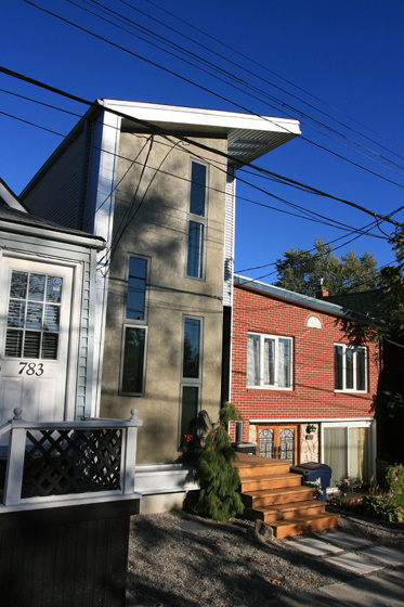 """The house reaches above the neighboring homes but remains architecturally united; its windows reference those of the house immediately next door. """"The neighbors' houses on either side vary in their setbacks, so we found a compromise that would work with b"""