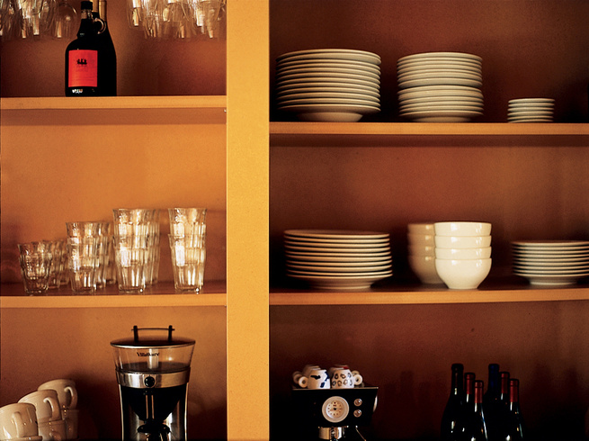 """The kitchen cabinets where the Scommegnas store their dishes are open, creating what Vetter calls a """"nonfussy, more direct approach to the storage of your daily items."""" Scommegna allows that a pair of doors easily could have been added without much troubl"""