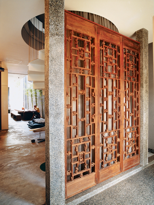 Modern shophouse ideas with carved antique panel doors.