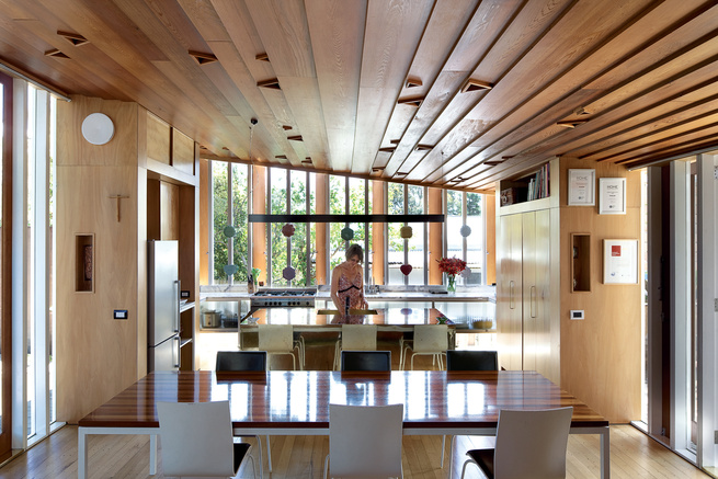 Melissa Schollum stands at the brass island bench in the kitchen. O'Sullivan, who designed and built the house, spent many hours creating the wooden joinery (including the tall, slender windows and their timber shutters) and the intricate ceiling. The cup