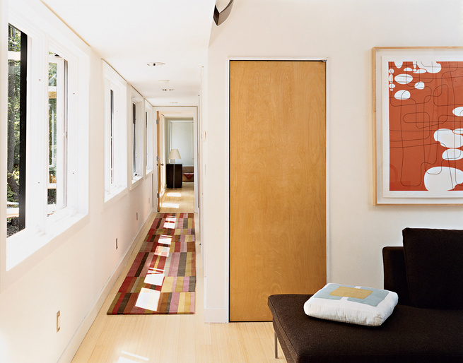 A view from the top of the stairs, past the office to the master bedroom. Sunlight filters through extensive fenestration to the hall, which features a runner by Emma Gardner. Artwork by Campbell Laird hangs over B&B Italia seating in the couple's office.