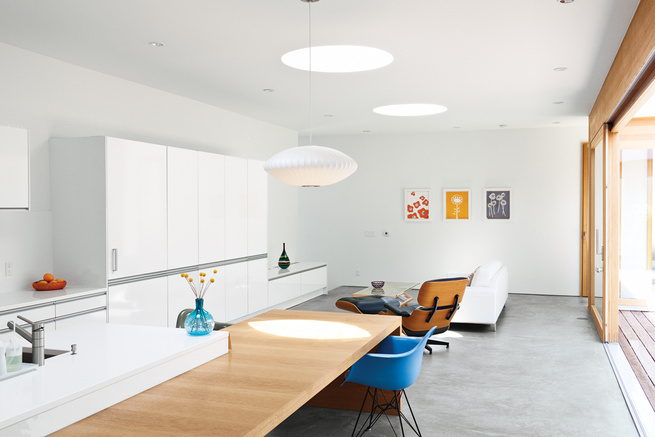 Modern prefab kitchen with white walls and Eames lounge chair