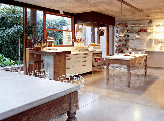 In the kitchen, buffed concrete floors, chrome globe lights, and a fleet of Bertoia chairs comprise a sleek backdrop for quirkier pieces like the marble-topped wooden tables from a Catholic school, snagged at a local flea market. The secret to the spare,