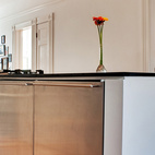 """Chris's original design consisted of only the island, which houses two Fisher Paykel dish drawers as well as a 24-inch gas oven and cooktop and two under-counter fridges by De'Longhi. Danielle, however, urged him to create a framed kitchen area so the living room on one side (shown here in the background) and the dining room on the other wouldn't bleed into each other as a single space. """"That's how the canopy was born,"""" Chris says. In addition to semi-enclosing the kitchen with the lowered, painted ceiling and partial wall, the canopy hides structural elements and the Broan hood for the cooktop. Photo by Kate McElwee."""