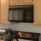 Chris removed the existing cabinets, microwave, oven, and stove from the cutout in the kitchen and filled it in with Ikea cabinets to create a flush wall that runs nearly the entire length of the public space.
