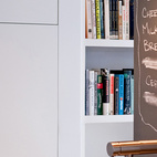 """Chris painted the partial wall (above the Vigo Industries sink and Cifial faucet) in Rust-Oleum chalkboard paint. """"It's kind of hokey,"""" he says, """"but I actually do use it."""" Most recently on the board: """"bread"""", """"OJ"""", """"milk"""" (crossed off), and """"mayonnaise"""" (crossed off). """"It's convenient when we're cooking and run out of stuff. We write it down and then transfer it to the grocery list later,"""" Chris says. Up next for Chris are a cottage project in Ontario, Canada, and a loft renovation in Boston. But with two of their own kitchen renovations completed within the past two years, the Greenawalts are now ready to rest and stay put in their own home and savor the results. Photo by Kate McElwee."""