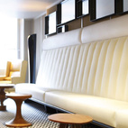 """The overlapping-decade approach is in full effect in the lobby, where mod wooden tables sculpted from oak, beech, and elm line a white leather banquette. Overhead, playful round chandeliers (""""reminiscent of large Camembert cheese of various sizes,"""" according to hotel literature) light the way from the front door to the reception desk."""