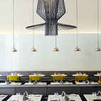 In the Americano restaurant, the walls—one in reflective black, the other in white lacquered glass—create a striking backdrop for the marble tables, yellow felt and khaki cloth chairs, and black leather banquettes that line the space. The large suspended lights from Foscarini provide sculptural interest and are balanced out by the smaller glinting lights from Tom Dixon. Despite its name, Mediterranean cuisine is the specialty here, crafted by chef Olivier Reginensi. Dishes are seasonal and organic and reflect influences from Southern France and Latin America. The restaurant spills onto the patio, where people enjoy meals al fresco.