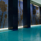 The rectangular indoor pool is the centerpiece of the 1000-square-meter Akasha Wellbeing Center. It's bordered by deep violet walls, lounge chairs, and tall columns.
