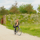 The cemetery, with its verdant landscape and monumental sculpture, can easily be confused with a public park. During my time there, many people at Friedhof-Riem were on foot and bike—here, a friendly Bavarian waves as I capture her on film.  Photo by: Bret RobinsCourtesy of:
