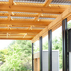 """Along the large porch/breezeway are bifacial solar panels (and a few Bertoia chairs). The panels collect direct sunlight from above and reflected light from below to increase the amount of energy created, which compensates for the flatness of the roof (not the optimal angle for typical solar panels). """"One concern people have about solar panels is that they often look like an afterthought,"""" says Davd Lee, one of the students who designed and built the home. Here they're integrated with the overall design and don't stick out like a sore thumb.Photo courtesy of the DOE.  Courtesy of: Foto©Jim Tetro/Jim Tetro Photog"""
