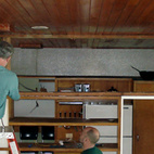 "One of the major changes to the house when it was rebuilt in 1950 was the raised height of the kitchen wall. ""Extending the wall up disguised the line of the butterfly ceiling,"" says Altman. Here, a team of craftsmen commissioned by the RBF works on deconstructing the upper portion of a non-lode bearing wall separating the kitchen from the living room. Photo courtesy of the Rockefeller Brothers Fund."